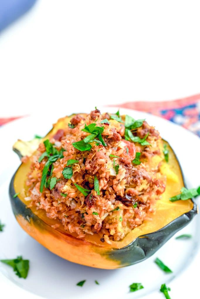 Overhead closeup of beef and bulgur Moroccan-style stuffed acorn squash on a white plate topped with chopped parsley