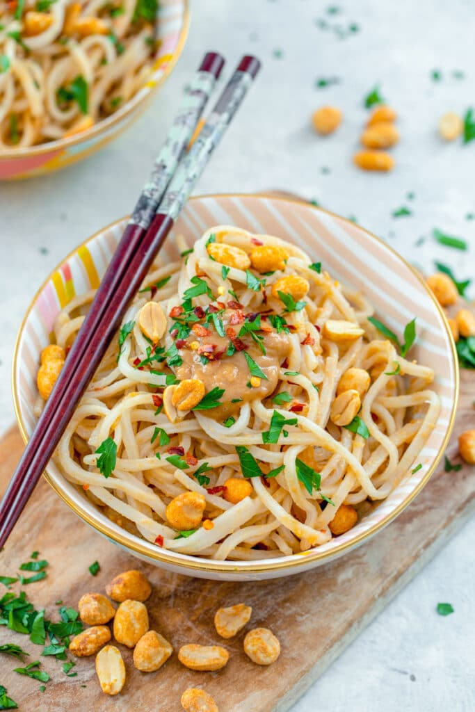 Closeup view of a bowl of noodles with peanut sauce with chopsticks on top with peanut and cilantro all around