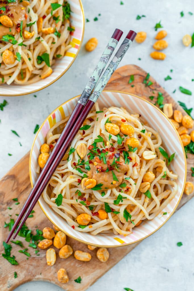 Overhead view of a bowl of noodles with peanut sauce with chopsticks on top and peanuts and cilantro all around, second bowl of noodles in the background