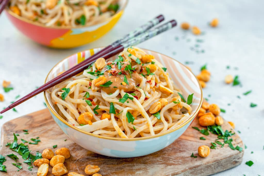 Landscape head-on view of a bowl of noodles with peanut sauce with chopsticks and cilantro and peanuts all around