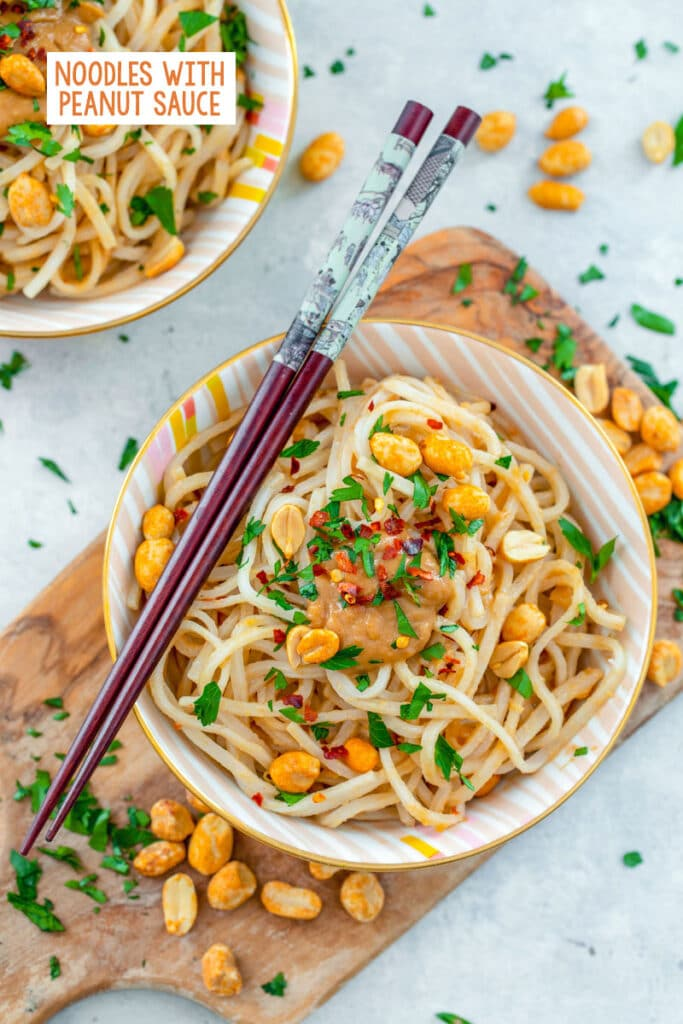 Overhead view of a bowl of noodles with peanut sauce with chopsticks on top and peanuts and cilantro all around, second bowl of noodles in the background, and recipe title at top of image