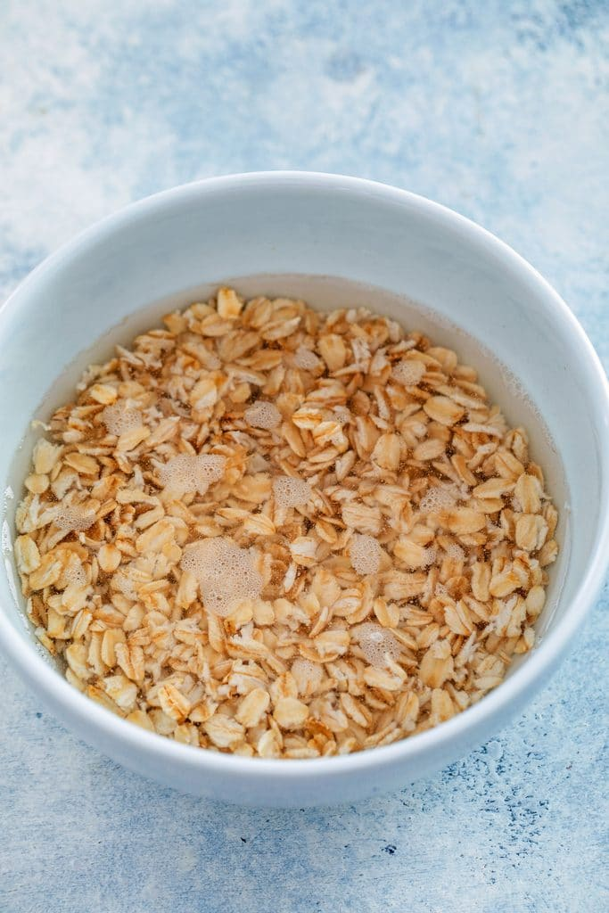 Overhead view of a white bowl of old-fashioned oats and water before going into the microwave