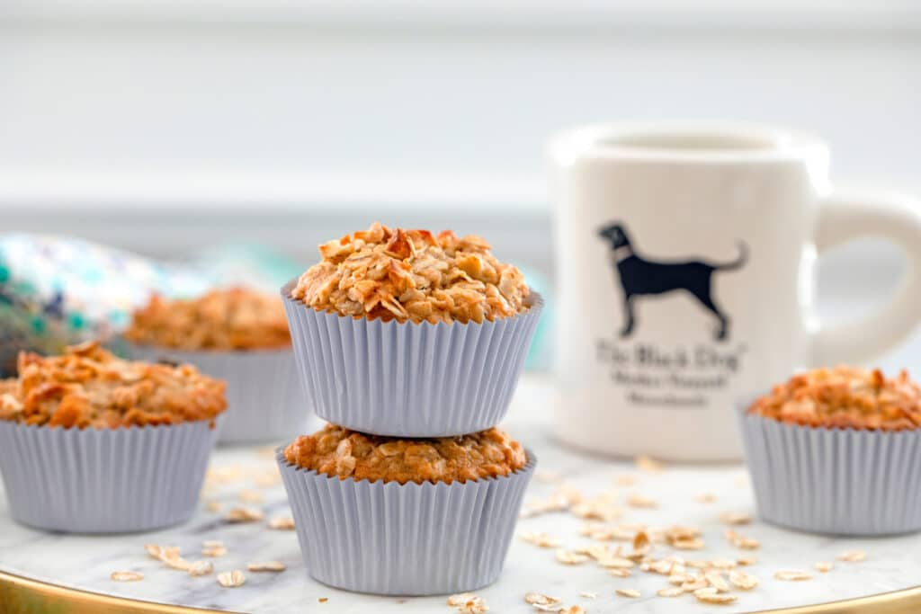 Head-on landscape view of multiple oatmeal raisin cookie muffins on marble tray with cup of coffee in the background