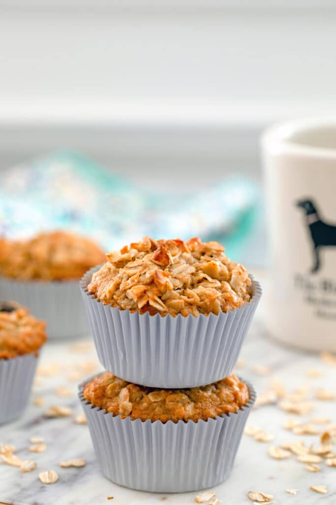 Head-on close-up of two oatmeal raisin cookie cupcakes on top of each other with more muffins, oats, and cup of coffee in the background