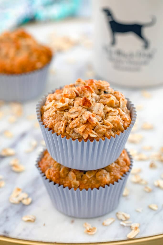 Close-up view of two oatmeal raisin cookie muffins stacked on each other with oats and a mug of coffee in the background