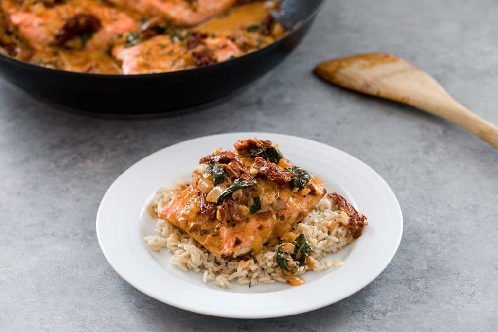 Landscape view of plate with creamy chipotle salmon set on a bed of brown rice with skillet and spoon in background