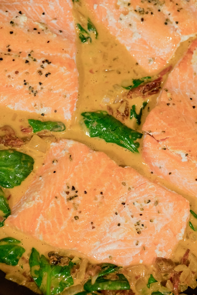 Salmon cooking with spinach and sun-dried tomatoes and sauce in skillet