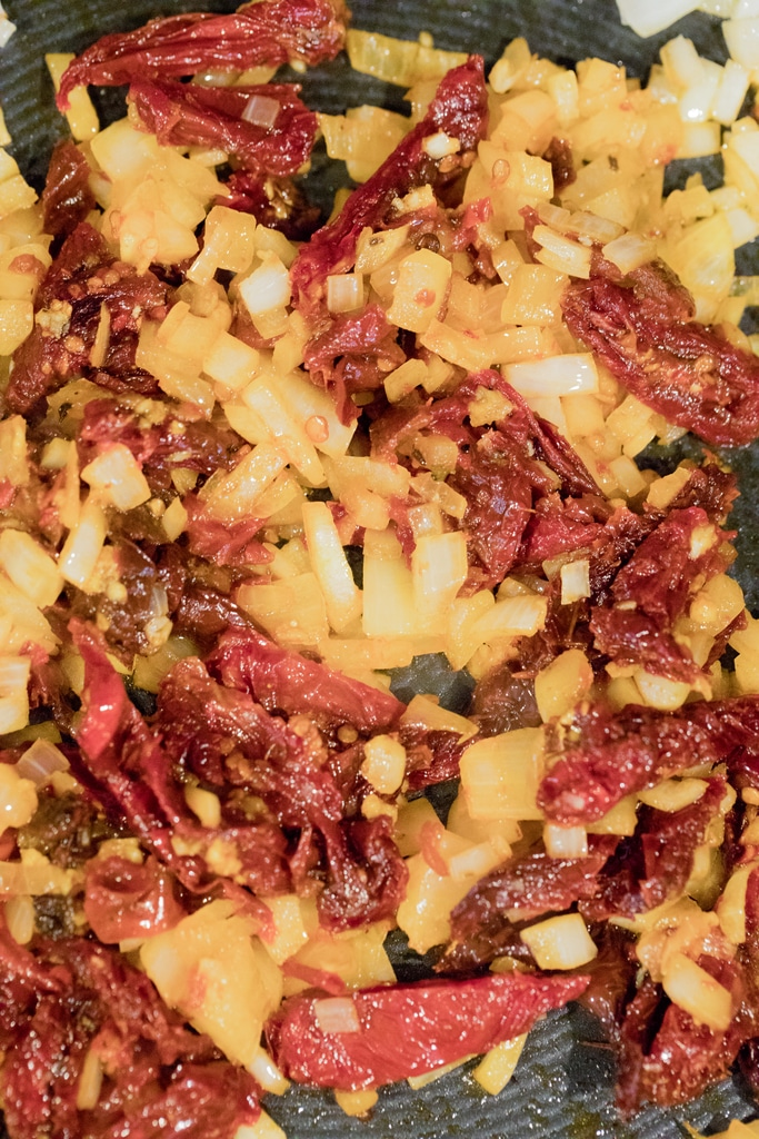 Chipotle peppers, sun-dried tomatoes and onions cooking in skillet