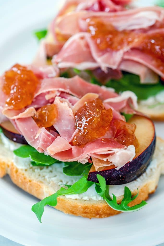 Up-close view of open-faced prosciutto and plum sandwiches with fig spread drizzled on top