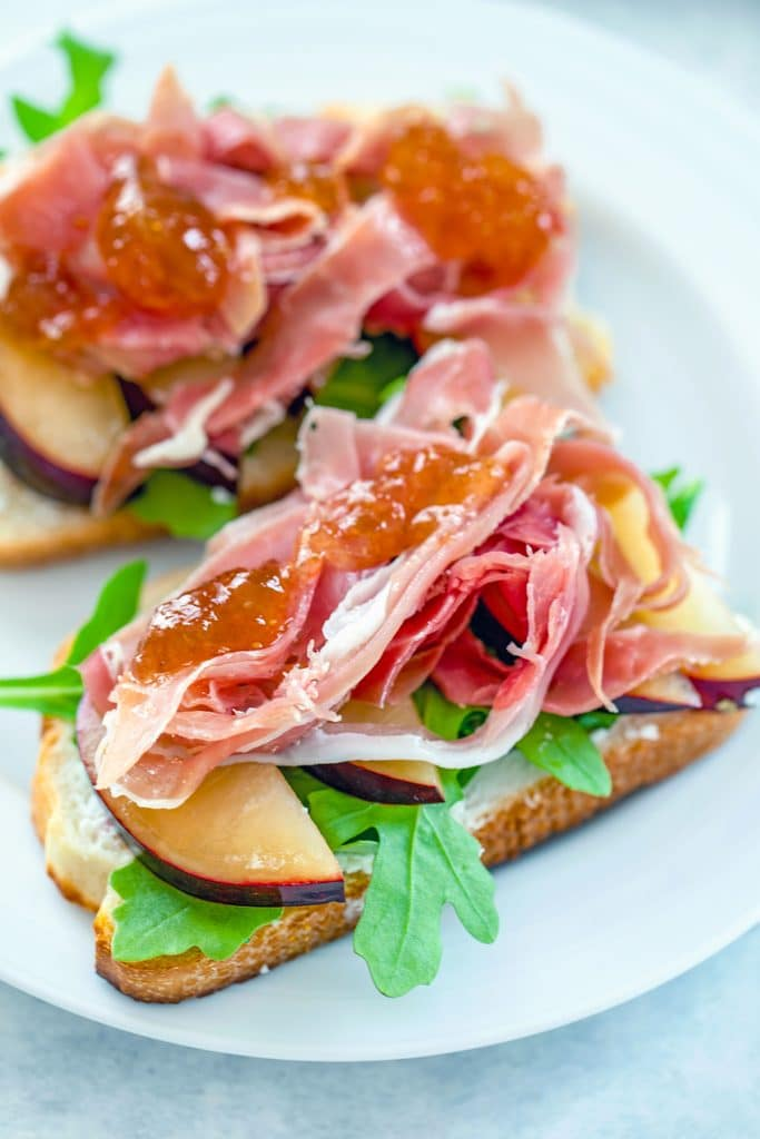 Head-on view of two open-faced prosciutto and plum sandwiches topped with fig ginger spread on a white plate