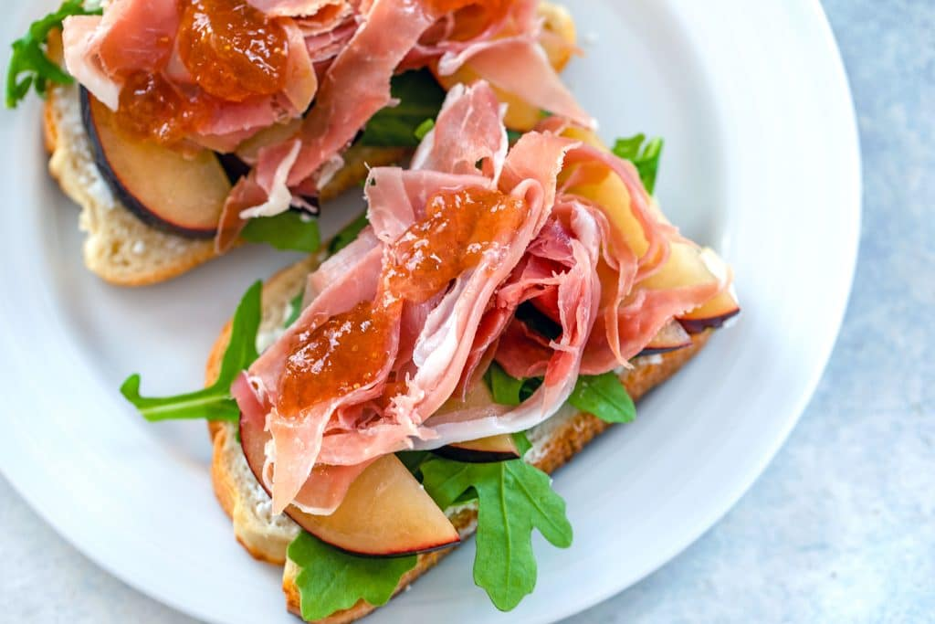 Landscape overhead view of open-faced prosciutto and plum sandwiches topped with fig ginger spread on a white plate
