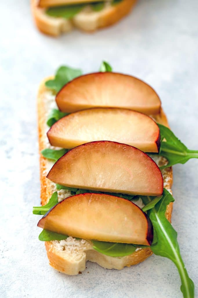 Overhead view of open-faced sandwich spread with goat cheese and topped with arugula and sliced plums