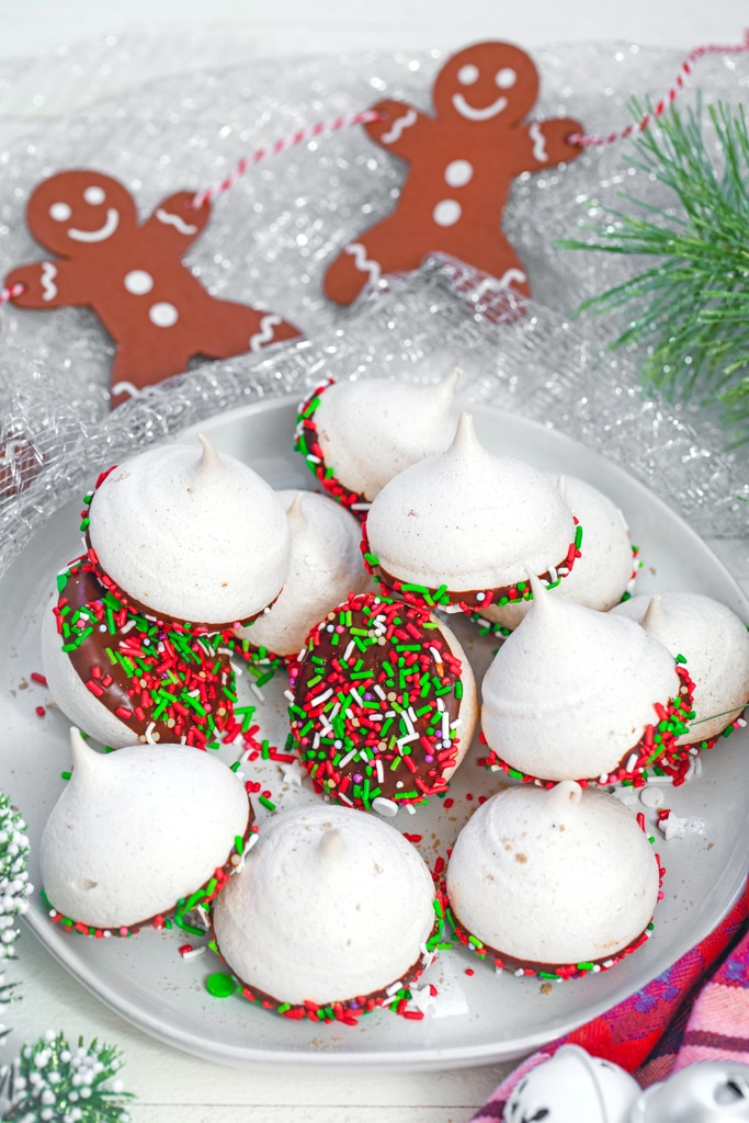 Overhead view of a plate full of orange gingerbread meringues dipped in chocolate with red and green sprinkles with gingerbread men decorations in the background and holly all around
