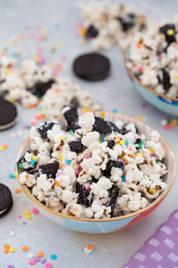 Head-on view of Oreo funfetti popcorn with colorful sprinkles in a bowl with Oreo cookies and more popcorn and sprinkles in background