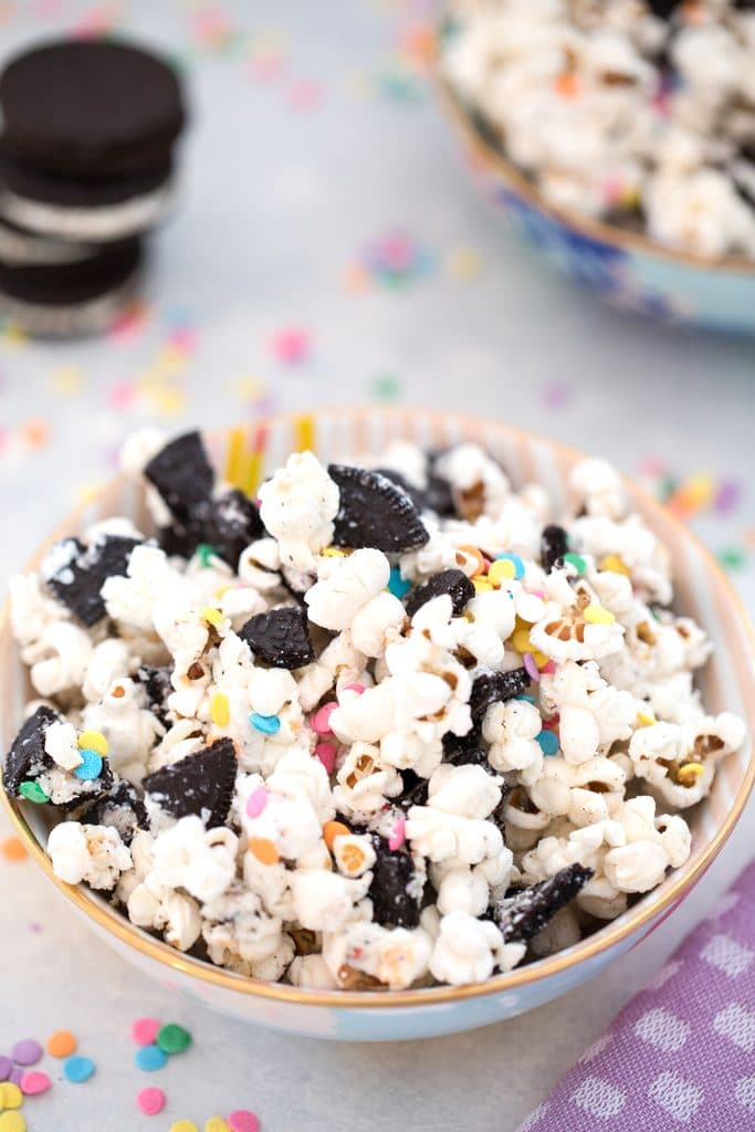 Overhead closeup view of Oreo funfetti popcorn with colorful sprinkles with stack of Oreo cookies and more sprinkles in the background
