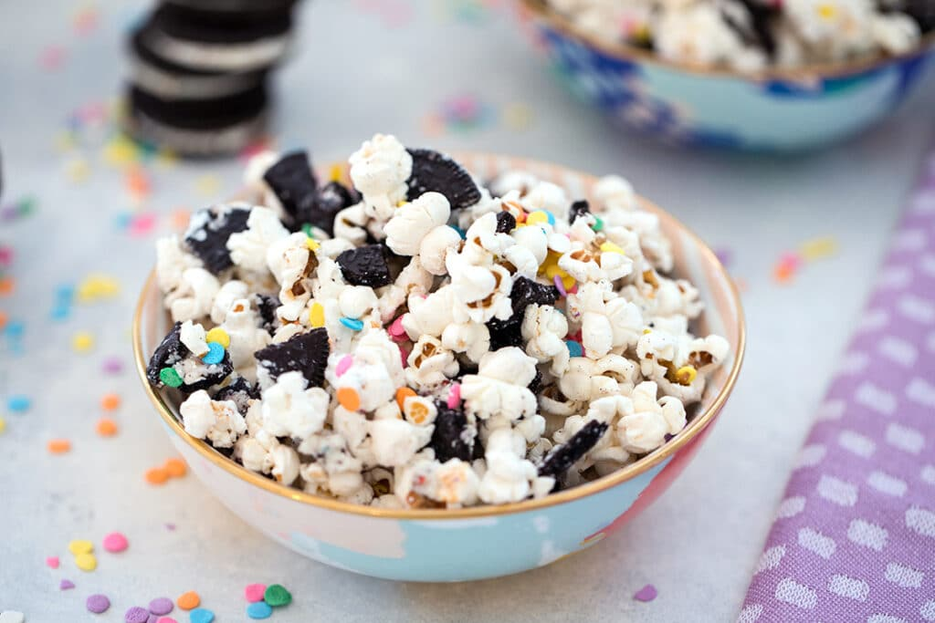 Landscape view of Oreo funfetti popcorn with colorful sprinkles with stack of Oreo cookies, more sprinkles, and second bowl of popcorn in the background