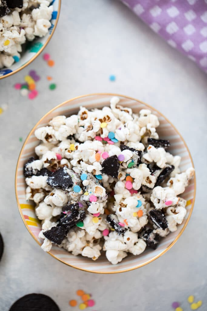 Bird's eye view of a bowl of Oreo funfetti popcorn with colorful sprinkles with second bowl of popcorn and more sprinkles in the background