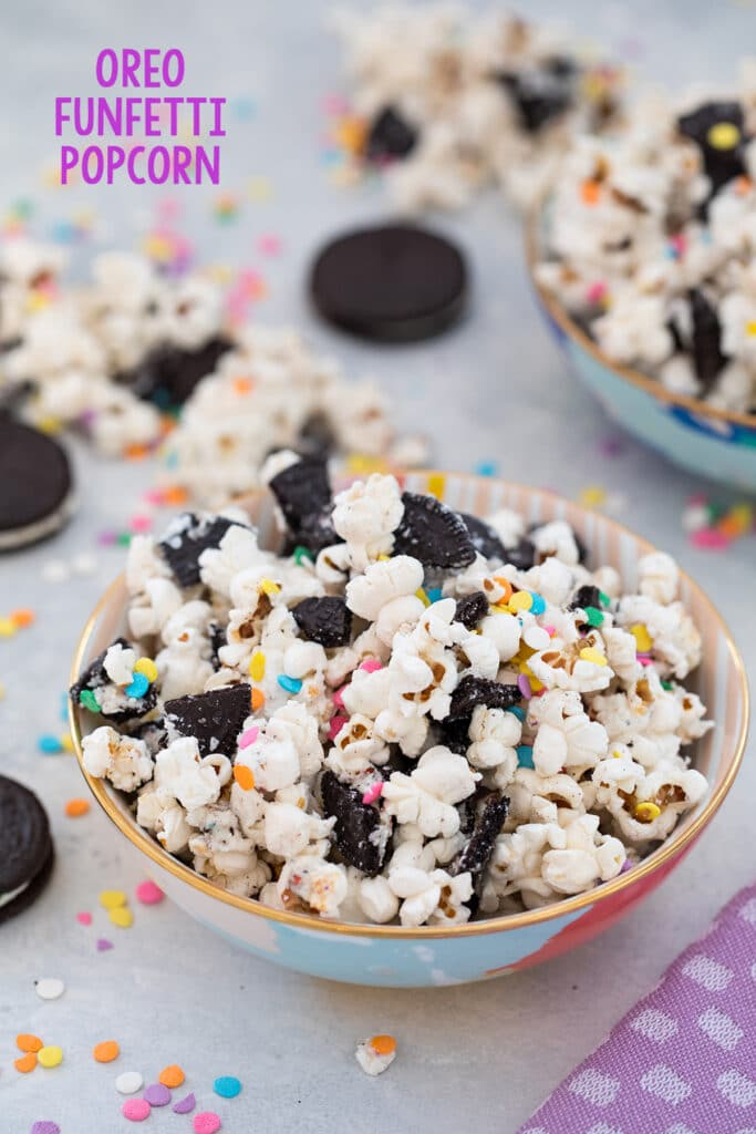 Head-on view of Oreo funfetti popcorn with colorful sprinkles in a bowl with Oreo cookies and more popcorn and sprinkles in background and recipe title at top