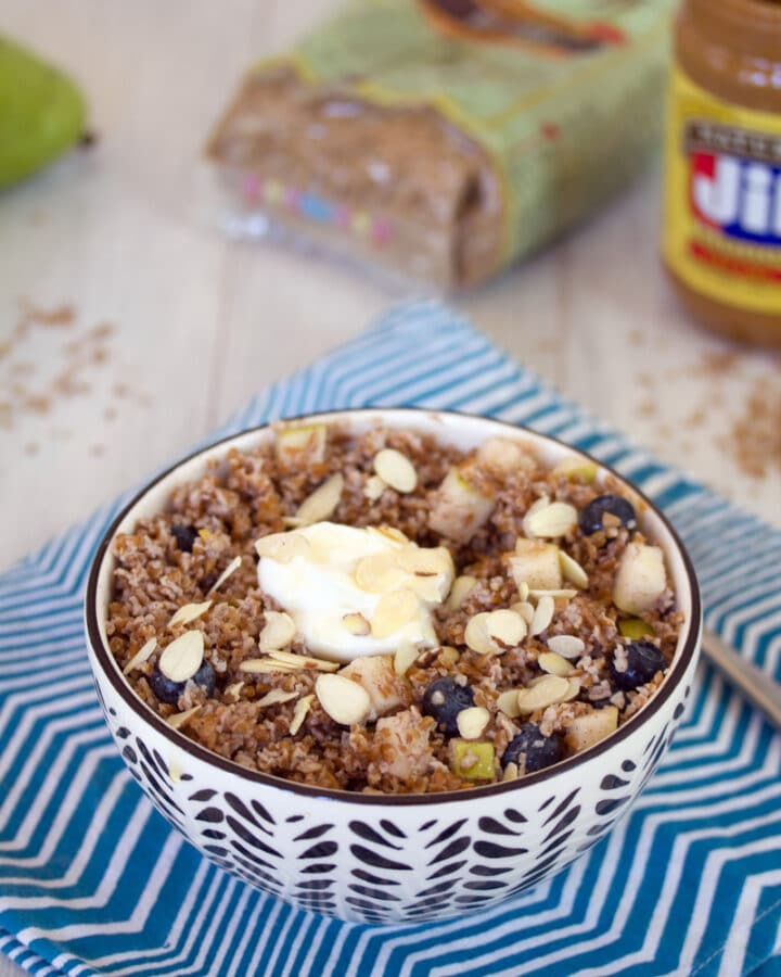 Head-on view of an overnight bulgur breakfast bowl with pears and blueberries with bulgur and peanut butter in the background