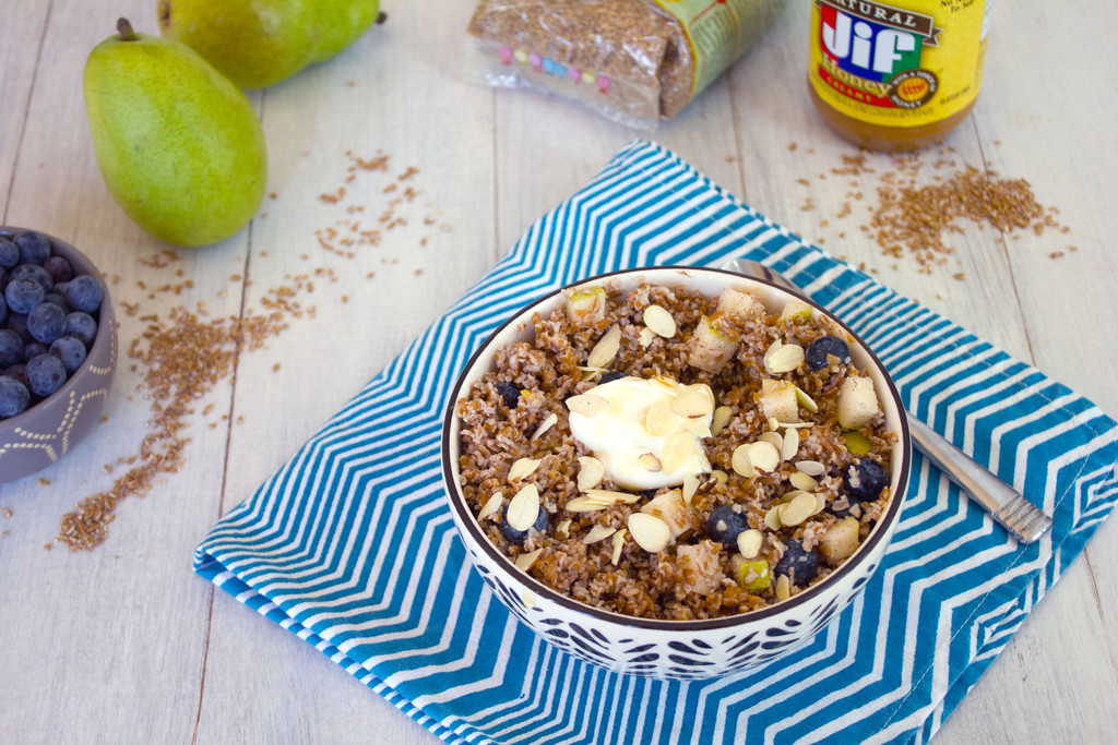 Landscape overhead view of an overnight bulgur breakfast bowl with pears and blueberries with bulgur, pears, and peanut butter in the background