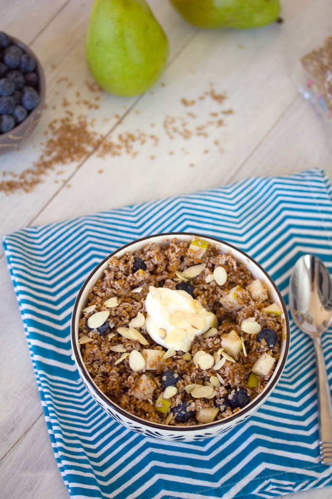 Overhead view of an overnight bulgur breakfast bowl with spoon, pears and blueberries with bulgur and peanut butter in the background