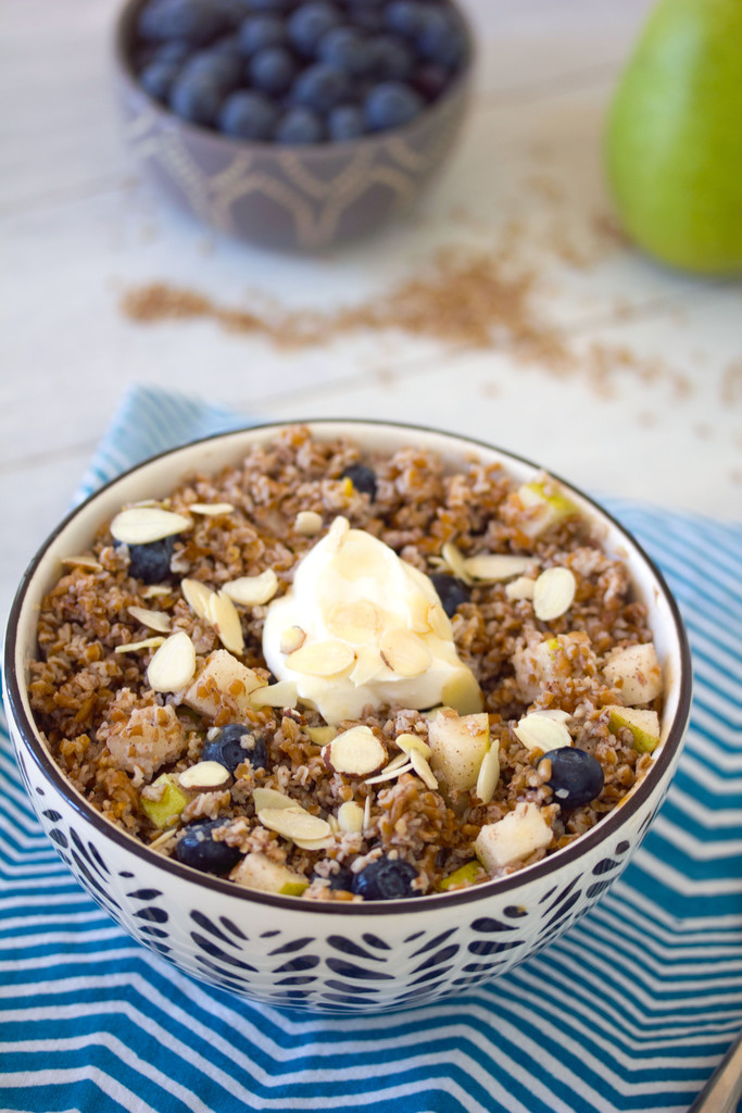 Overhead closeup view of an overnight bulgur breakfast bowl with pears and blueberries