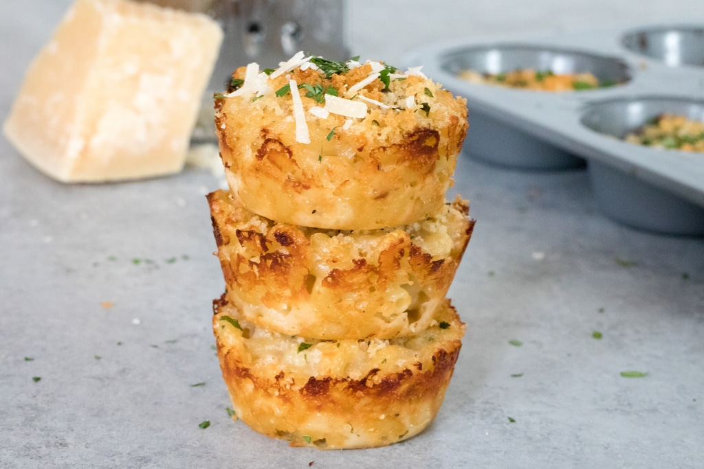 Landscape head-on view of a stack of three mac and cheese bites with block of parmigiano reggiano and grater in background and tin of more mac and cheese bites
