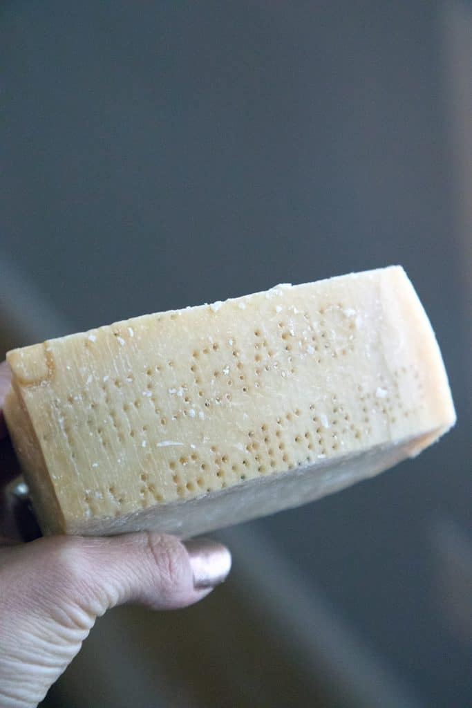 Hand holding up block of cheese to see parmigiano reggiano dot text on rind