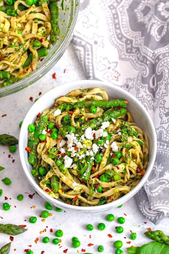 Overhead view of a bowl of pasta with green vegetables, herbs, and feta with serving bowl in the background and asparagus, peas, and red pepper flakes scattered around