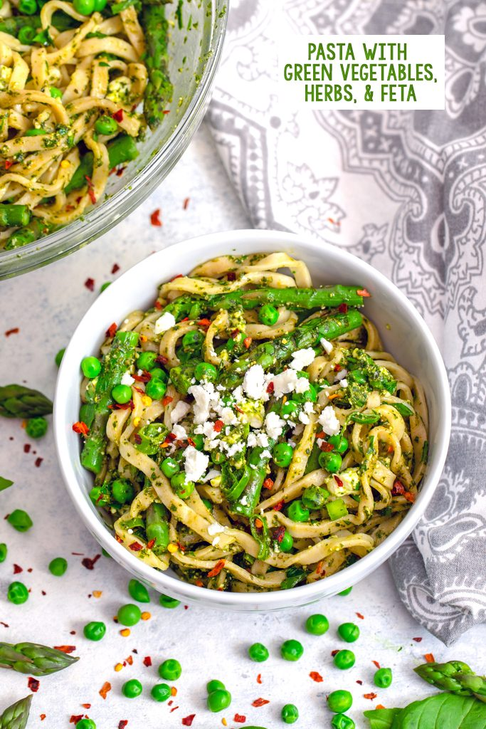 Overhead view of a bowl of pasta with green vegetables, herbs, and feta with serving bowl in the background, asparagus, peas, and red pepper flakes scattered around and recipe title at top