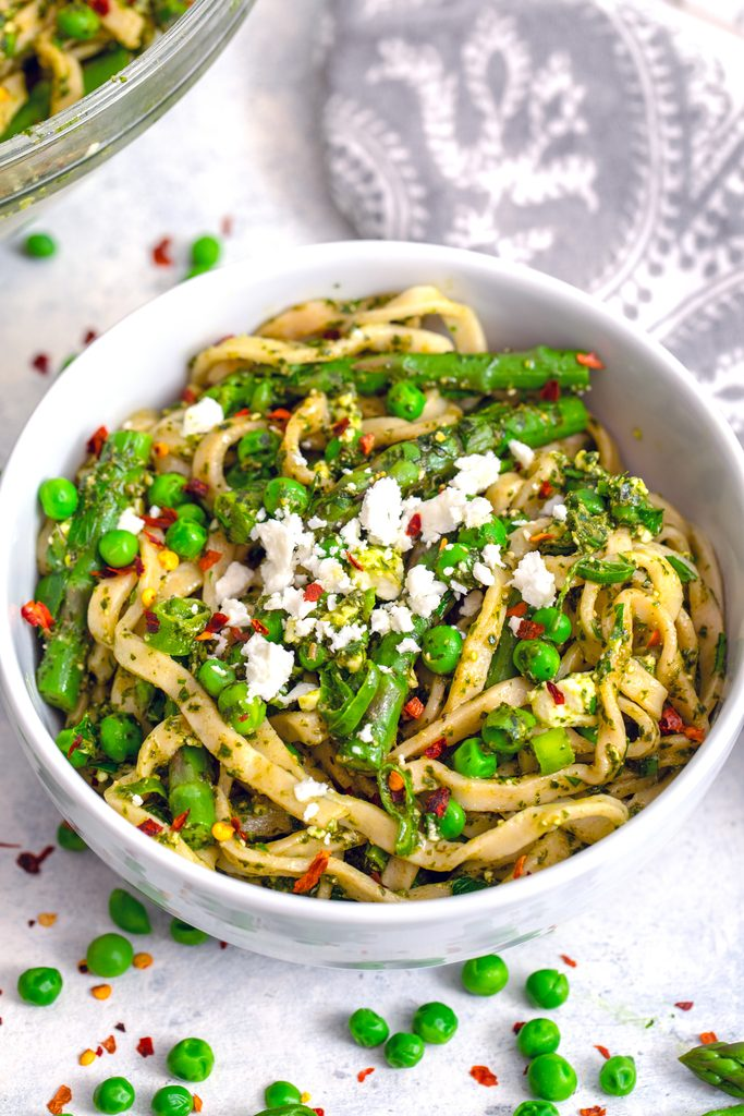 Head-on closeup view of a bowl of pasta with green vegetables, herbs, and feta with peas and red pepper flakes scattered around