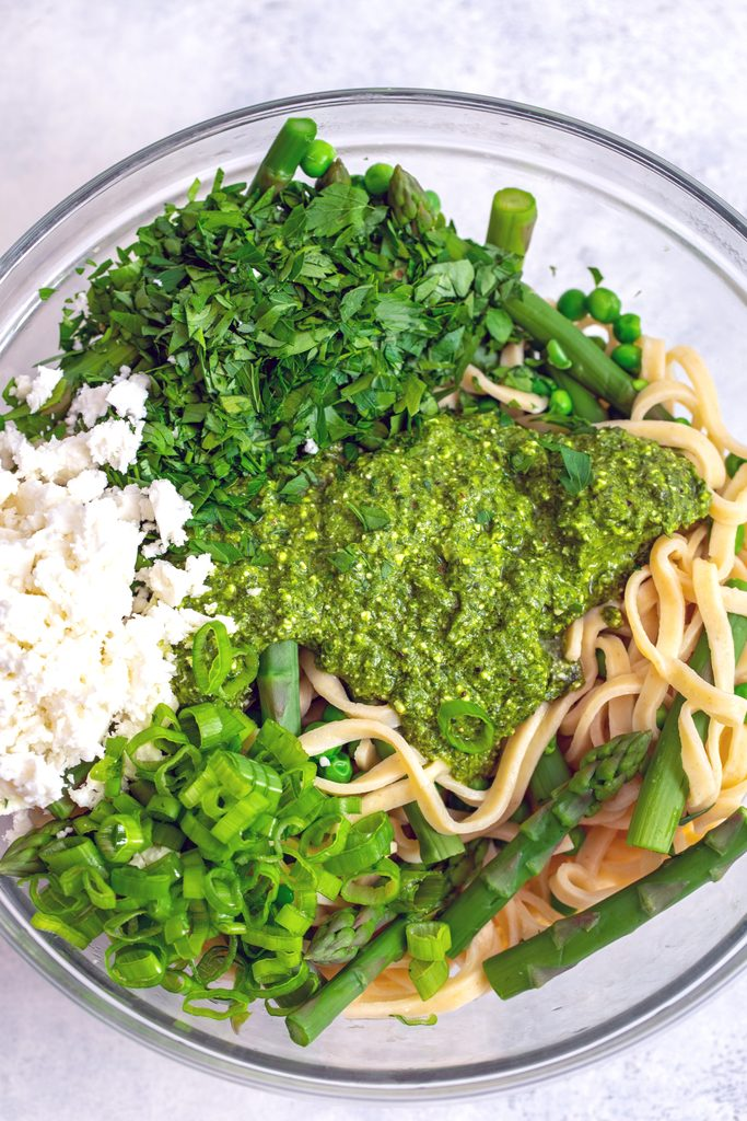 Overhead view of serving bowl with linguine, basil mint pesto, parsley, asparagus, peas, feta, and scallions in it