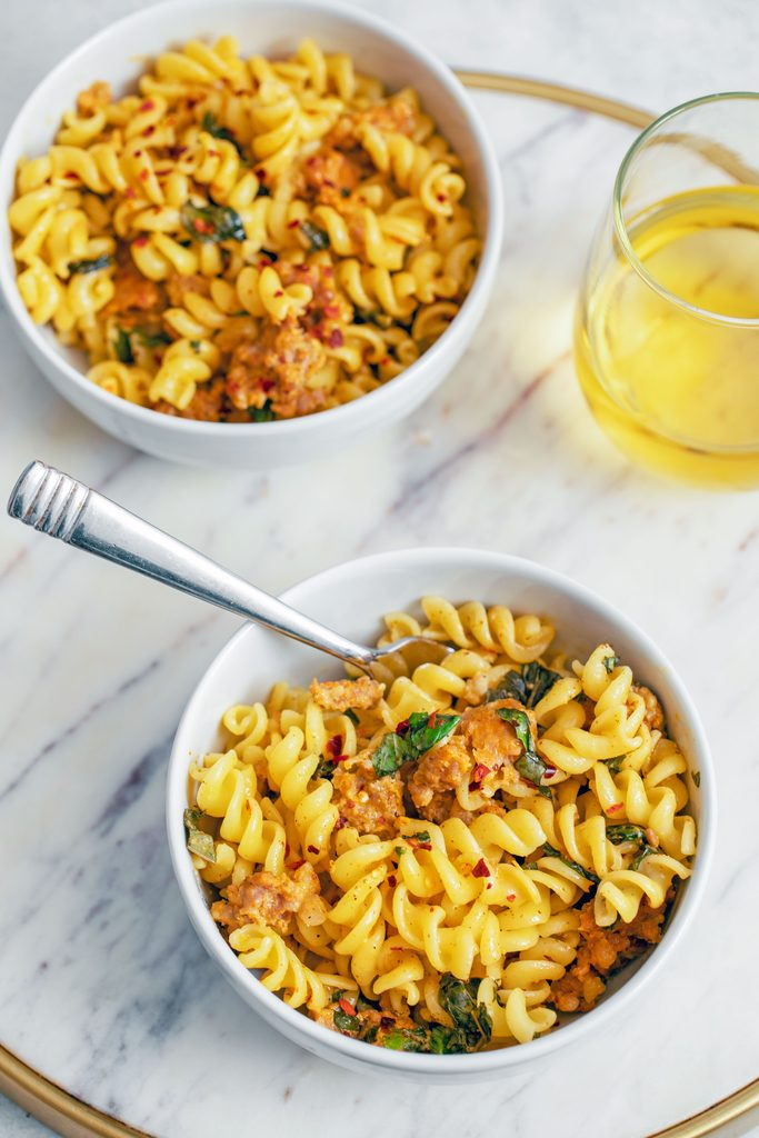 Overhead view of two bowls of pasta with spicy sausage, basil, and mustard on a marble surface with a fork and a glass of white wine