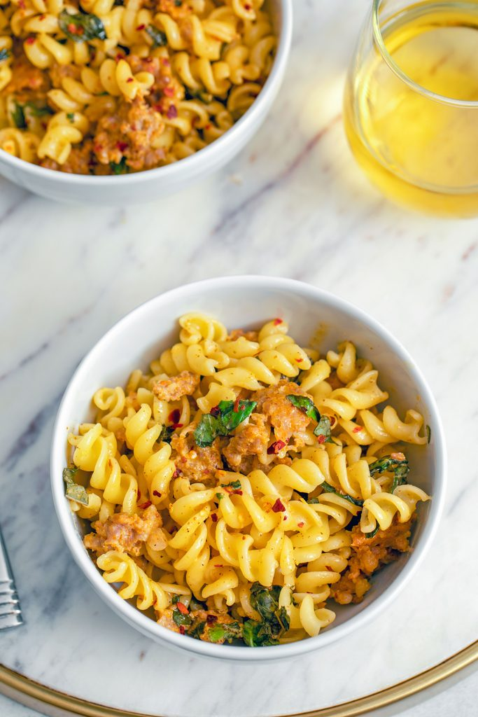 Overhead view of a bowl of pasta with spicy sausage, basil, and mustard on a marble surface with a second bowl and a glass of white wine in the background