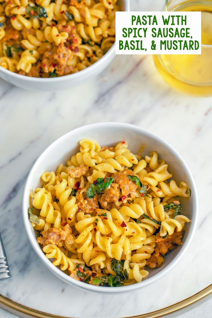 Overhead view of a bowl of pasta with spicy sausage, basil, and mustard on a marble surface with a second bowl and a glass of white wine in the background with recipe title at top