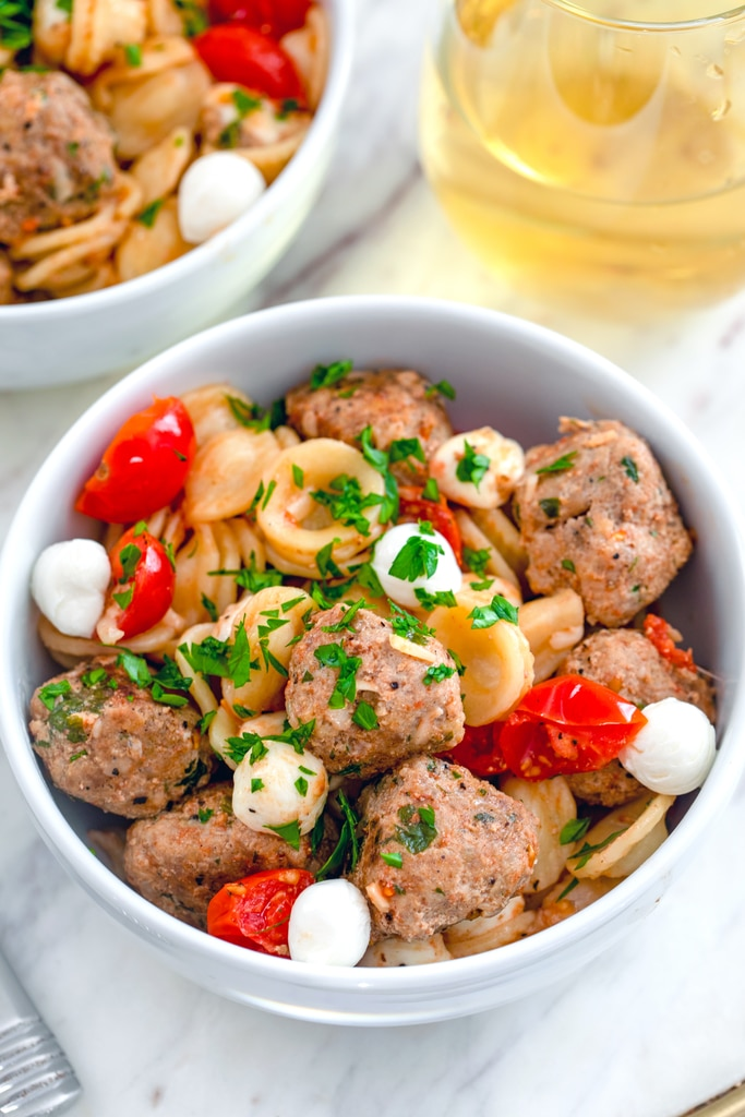Close-up view of bowl of pasta with turkey meatballs with mozzarella and tomatoes with glass of white wine in the background