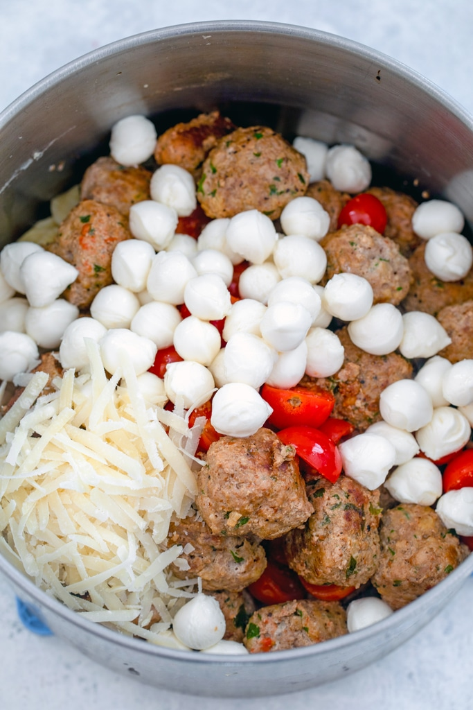 Turkey meatballs, mozzarella pearls, shredded parmesan, and tomatoes in saucepan with pasta