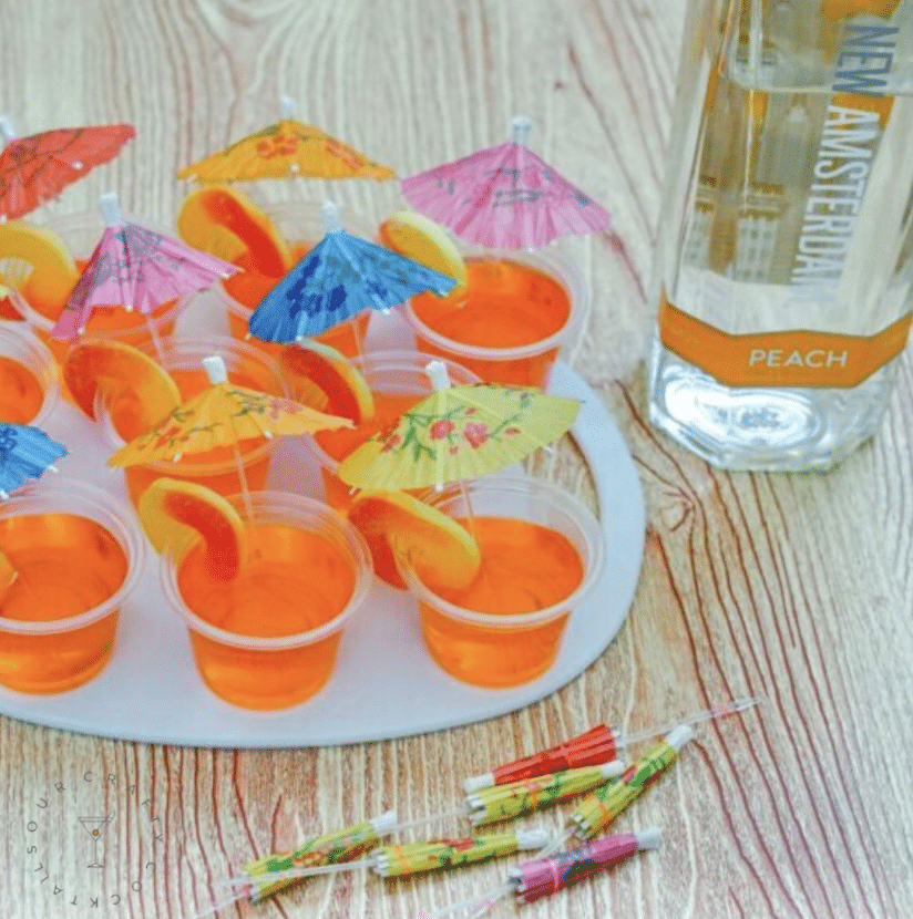 Peach jello shots in little cups with peach ring and paper umbrella garnish