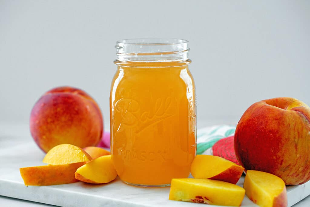 Landscape head-on view of a mason jar of peach simple syrup with whole peaches and peach slices in background