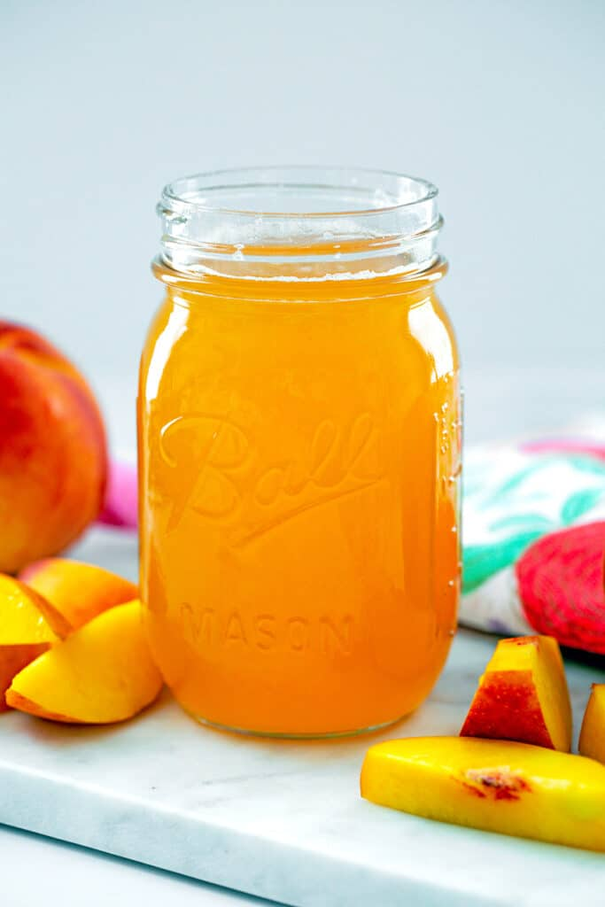 Head-on view of peach simple syrup in a mason jar with sliced peaches around