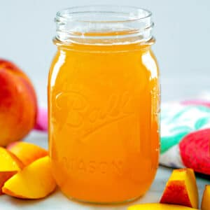 Head-on closeup view of peach simple syrup in a mason jar with sliced peaches around