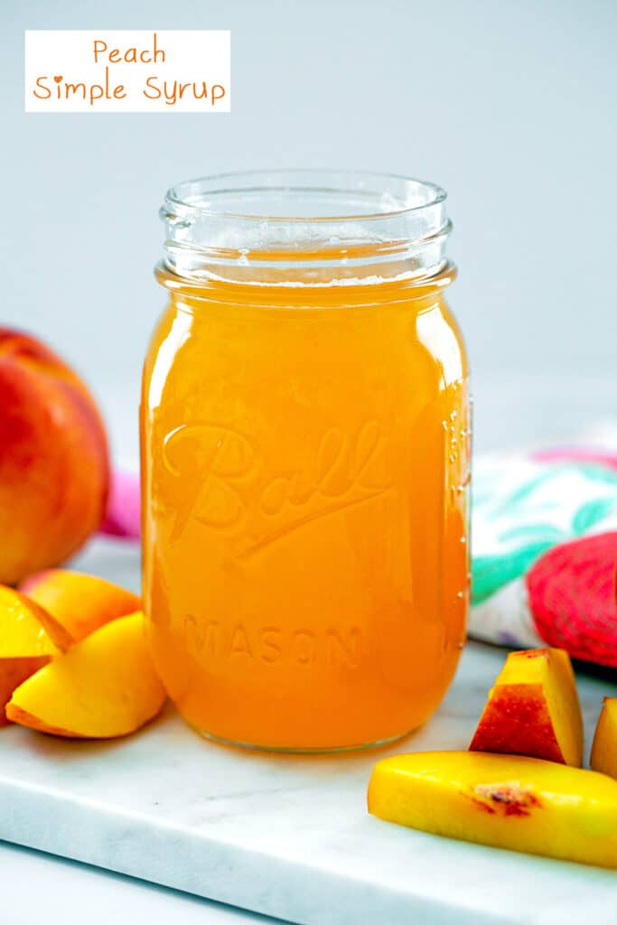 Head-on view of peach simple syrup in a mason jar with sliced peaches around and recipe title at top