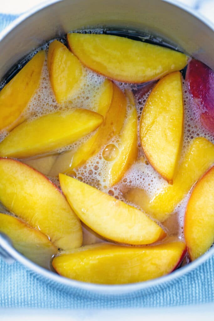Sliced peaches boiling in water and sugar in saucepan