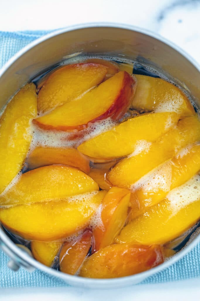 Softened peaches simmering in water and sugar in saucepan