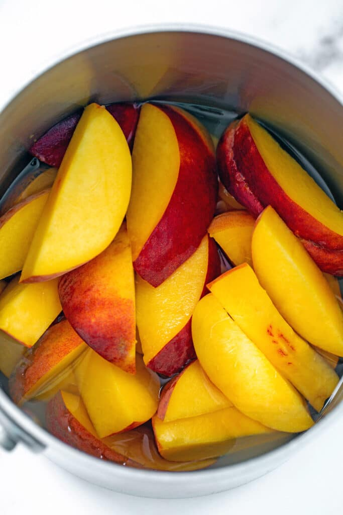 Overhead view of sliced peaches in saucepan with water and sugar