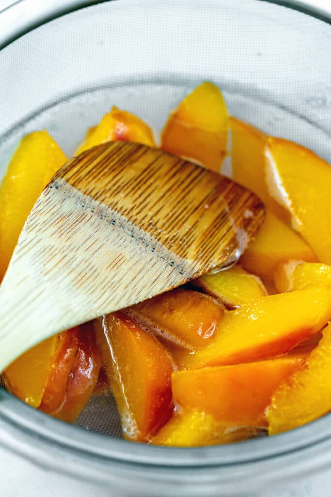 Softened peaches in strainer with a wooden spatula pressing down on them to extract juice