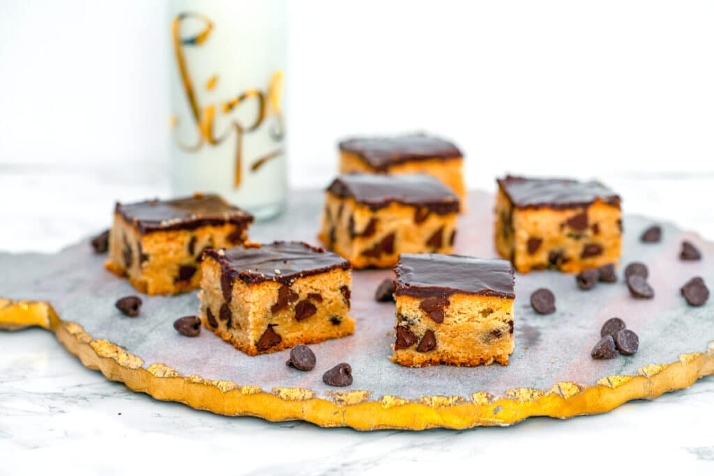 Landscape head-on view of multiple peanut butter blondes with chocolate ganache on a pretty platter with chocolate chips all around and bottle of milk in background