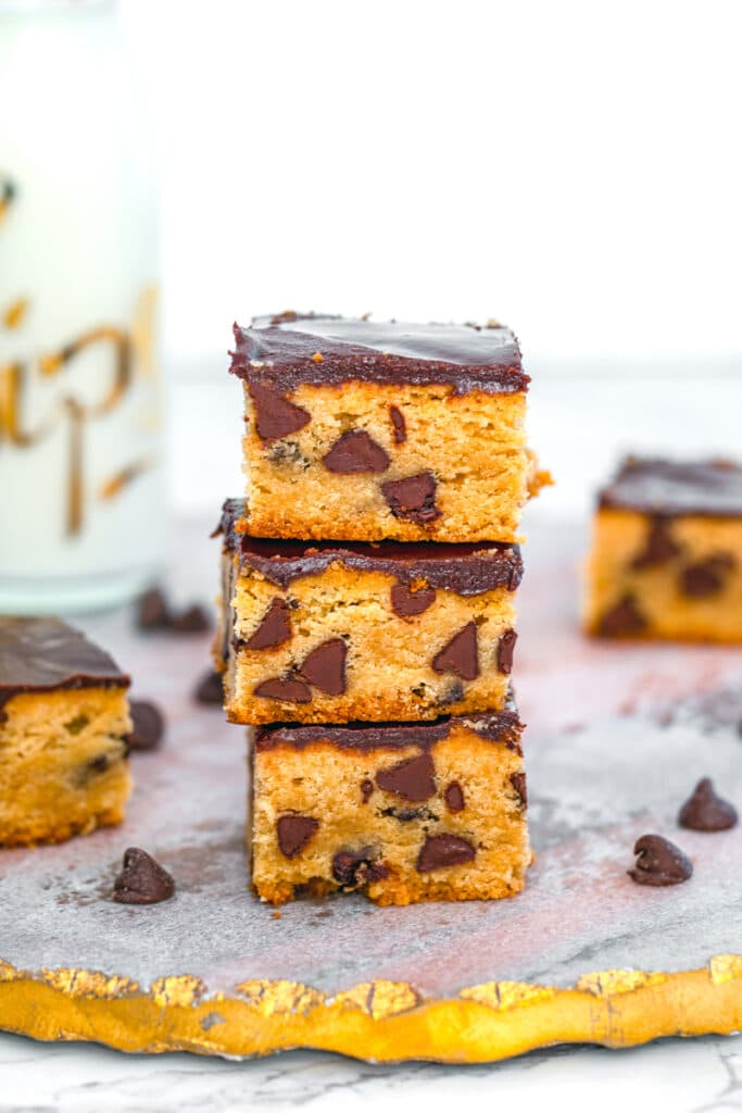 Head-on close-up view of a stack of peanut butter blondies with chocolate ganache and chocolate chips with more blondies and bottle of milk in the background