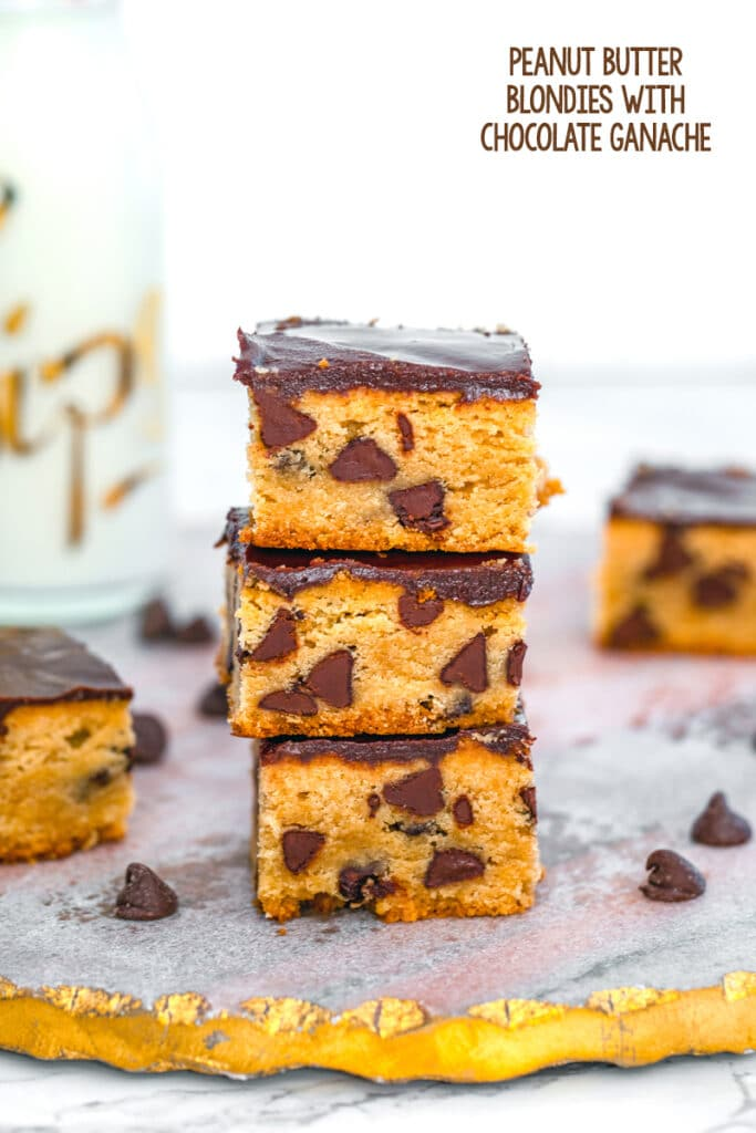 Head-on close-up view of a stack of peanut butter blondies with chocolate ganache and chocolate chips with more blondies and bottle of milk in the background and recipe title at top