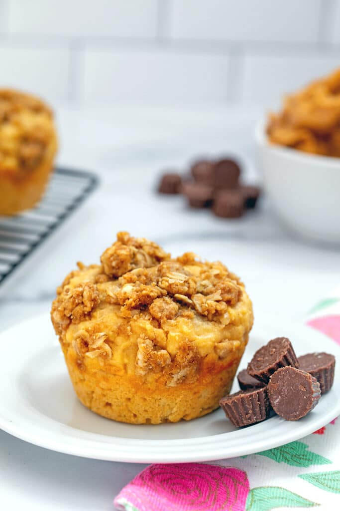 Head-on view of peanut butter chocolate muffin on a small white plate with mini peanut butter cups around and more muffins and bowl of peanut butter in background